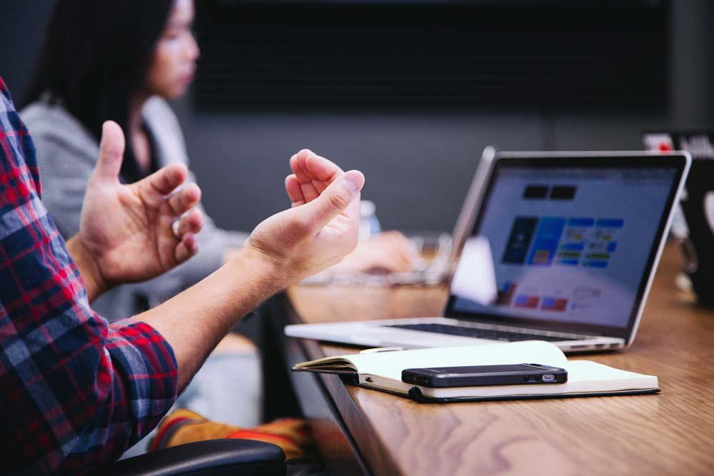 Nous trouvons des personnes en réunions. Elles sont assises avec un ordinateur devant elles et une des personnes s'exprime.