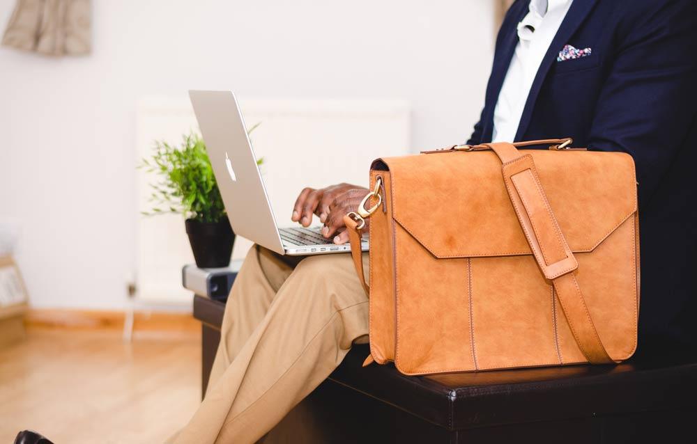 Cette image représente une personne assie dans un fauteuil. Elle est habillée en costume de traavil. A côté d'elle se trouve un sac pour y ranger ordinateur et dossiers. Sur ses genoux est posé un mac. La personne est en train de travailler, de pianoter quelque chose sur le mac.